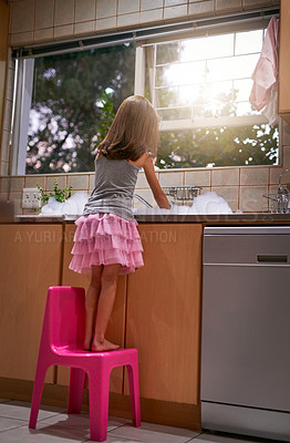 Buy stock photo Shot of a young girl standing on a chair to wash dishes at a kitchen sink