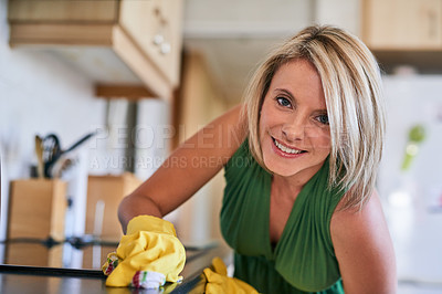 Buy stock photo Portrait of a young woman cleaning a kitchen surface