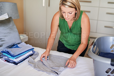 Buy stock photo Shot of a young woman folding up some laundry