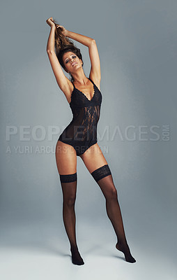 Buy stock photo Shot of an attractive young woman posing in a black bodysuit against a grey background