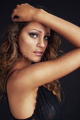 Buy stock photo Cropped shot of a beautiful young woman posing against a black background