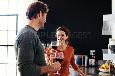 Buy stock photo Shot of a husband and wife drinking wine together in their kitchen