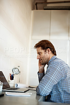 Buy stock photo Shot of a man talking on his phone while working on a laptop