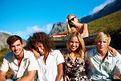 Buy stock photo Portrait of a group of young friends sitting on a car bumper while on a road trip together