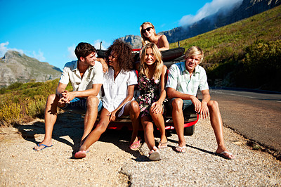 Buy stock photo Shot of a group of young friends sitting on a car bumper while on a road trip together