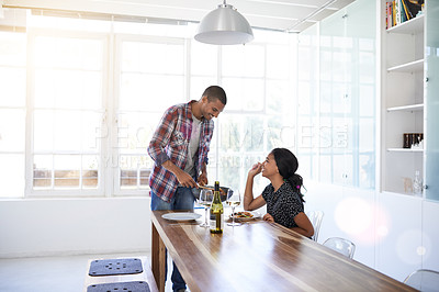 Buy stock photo Shot of a young man serving his wife dinner at their kitchen table