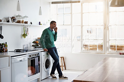 Buy stock photo Shot of a young man leaning on his kitchen counter talking on the phone