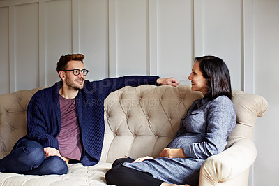 Buy stock photo Shot of a young pregnant woman talking with her husband on their sofa