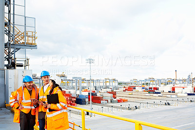 Buy stock photo Shot of three coworkers in protective workwear standing on a large commercial dock