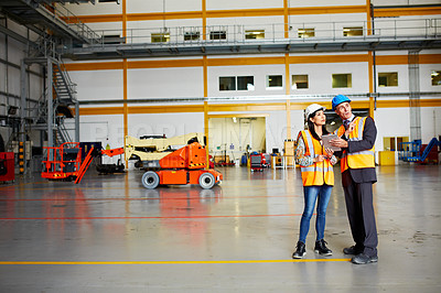 Buy stock photo Shot of two warehouse workers talking together over a digital tablet