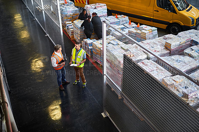 Buy stock photo High angle shot of two warehouse workers standing in a large warehouse