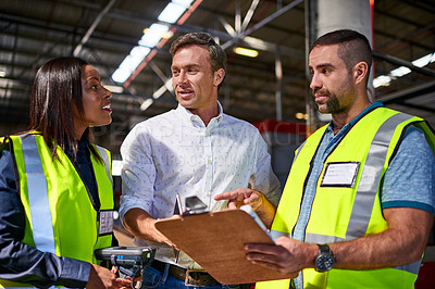 Buy stock photo Shot of three workers talking together over a clipboard inside of a warehouse