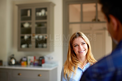 Buy stock photo Shot of a young woman talking to her husband in their kitchen