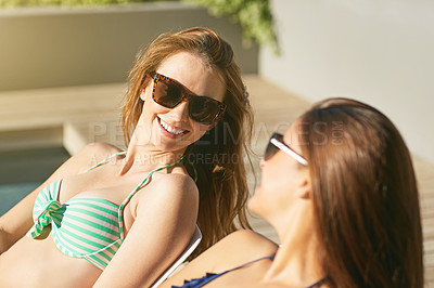 Buy stock photo Shot of two young woman suntanning by a swimming pool