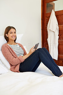 Buy stock photo Portrait of a young woman sitting on her bed using a digital tablet