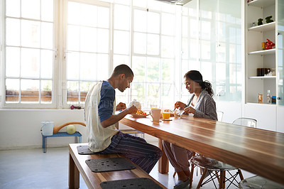 Buy stock photo Shot of a young couple eating breakfast together in their kitchen