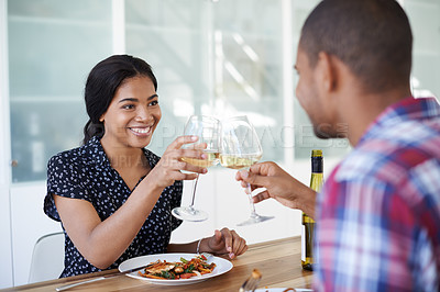 Buy stock photo Shot of a young couple toasting while eating dinner in their kitchen