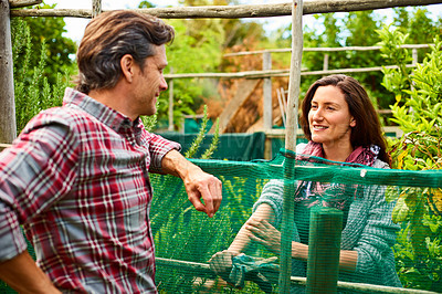 Buy stock photo Shot of a couple talking together while working in their organic garden