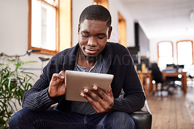 Buy stock photo Shot of a young man using a digital tablet while sitting in an office