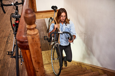 Buy stock photo Shot of a young man carrying his bike up the stairs