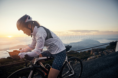 Buy stock photo Cropped shot of a young woman sending a text while cycling in the mountains