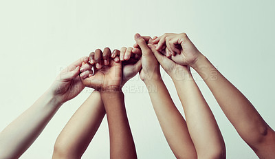 Buy stock photo Cropped shot of a group of people holding each others' thumbs with their hands raised