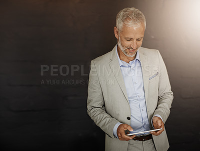 Buy stock photo Shot of a mature businessman using a digital tablet