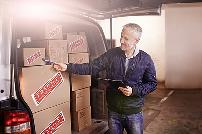 Buy stock photo Shot of a mature delivery man counting the boxes in his van