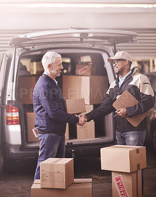 Buy stock photo Shot of two delivery men shaking hands next to a van filled with boxes