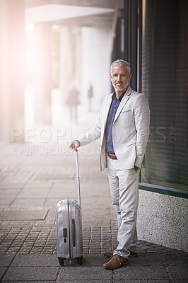 Buy stock photo Portrait of a mature businessman standing with a suitcase outside