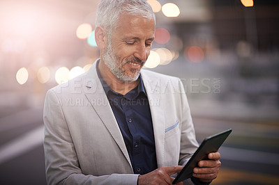 Buy stock photo Shot of a mature businessman using a digital tablet outside