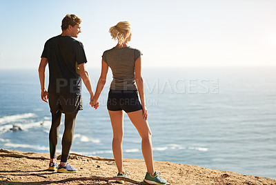 Buy stock photo Shot of a young couple looking at the view from the top of a mountain
