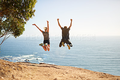 Buy stock photo Shot of a young couple jumping for joy after their workout