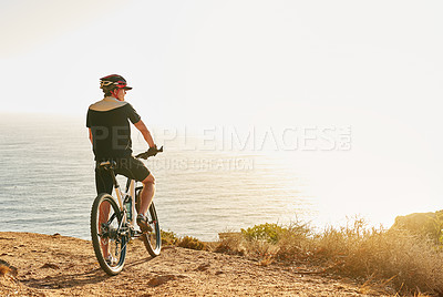 Buy stock photo Shot of a man admiring the view from a hilltop while out on a bike ride