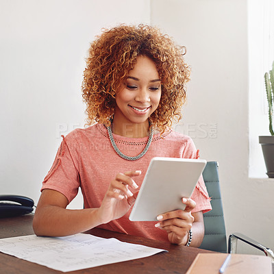 Buy stock photo Cropped shot of a designer using her tablet at the office