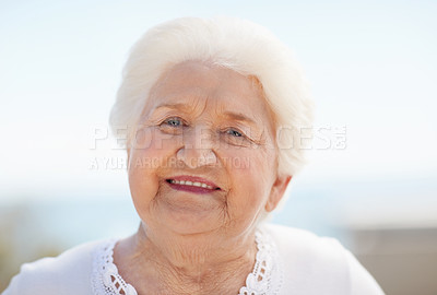 Buy stock photo Portrait of happy-looking senior woman standing outside and smiling at the camera