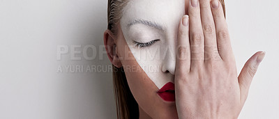Buy stock photo Shot of a beautiful woman wearing face paint and red lipstick against a plain background