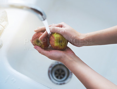 Buy stock photo Shot of a person washing apples at a tap