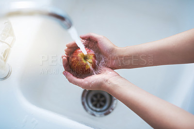 Buy stock photo Shot of a person washing an apple at a tap