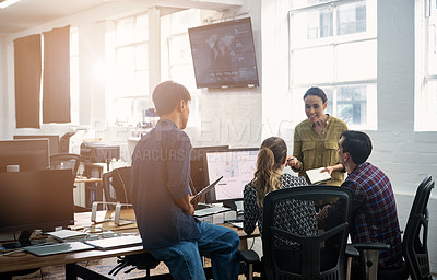 Buy stock photo Shot of a group of colleagues having an informal meeting in a modern office