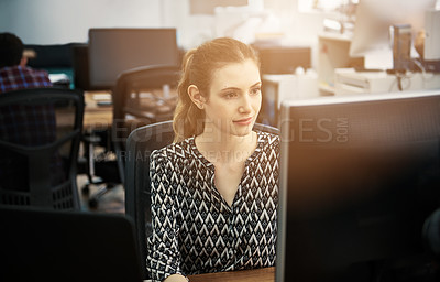 Buy stock photo Shot of a young woman using a computer at her desk in a modern office