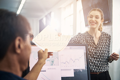 Buy stock photo Shot of a woman giving a document to her coworker in a modern office