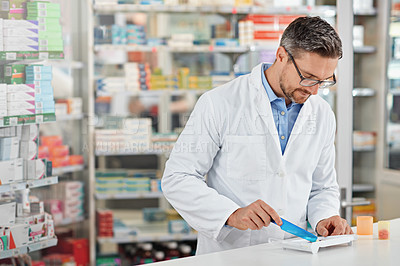 Buy stock photo Shot of a pharmacist counting medication. All products have been altered to be void of copyright infringements