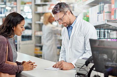 Buy stock photo Shot of a male pharmacist assisting a customer at the prescription counter. All products have been altered to be void of copyright infringements