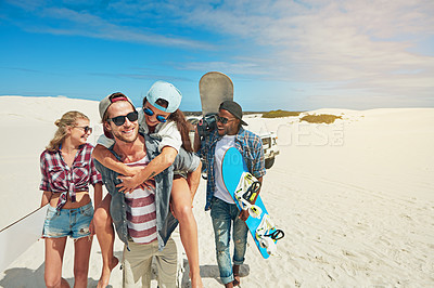 Buy stock photo Shot of a group of young friends sandboarding in the desert