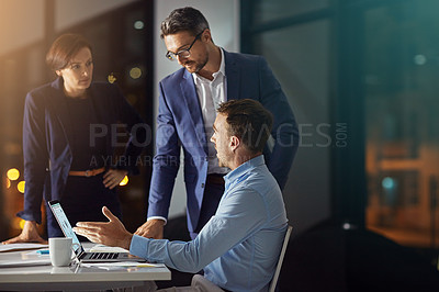 Buy stock photo Shot of a colleagues using a laptop together while woking late at the office