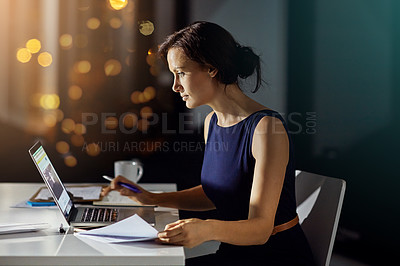 Buy stock photo Shot of a businesswoman using a laptop while woking late at the office