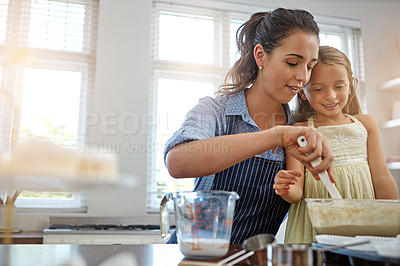 Buy stock photo Cropped shot of a mother and her daughter baking in the kitchen