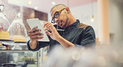 Buy stock photo Shot of a man talking on his cellphone in a coffee shop while using a digital tablet