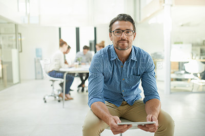 Buy stock photo Portrait of a mature man using a digital tablet at work with his team working in the background